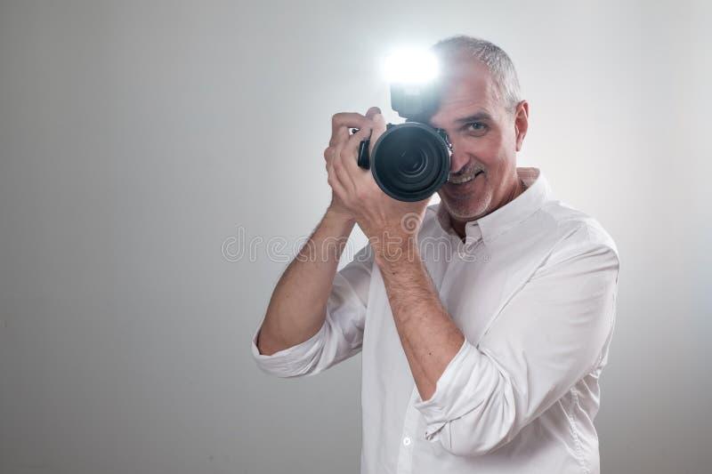 Studio strzał młody etniczny Azjatycki mężczyzna z kamerą przeciw brown tłu obrazy stock