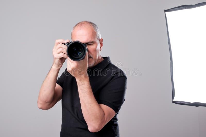 Studio strzał młody etniczny Azjatycki mężczyzna z kamerą przeciw brown tłu fotografia royalty free