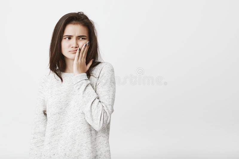Studio strzał młody piękny kobieta model z brown włosy, trzymający palmowy na policzku, wyraża nieszczęście, nużenie obraz royalty free