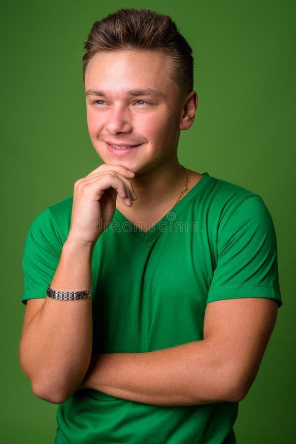 Studio strzał młody przystojny mężczyzna przeciw zielonemu tłu zdjęcie stock