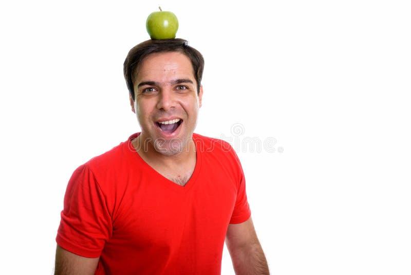 Studio strza? m?ody szcz??liwy Perski m??czyzna ono u?miecha si? z zielonym jab?kiem fotografia royalty free