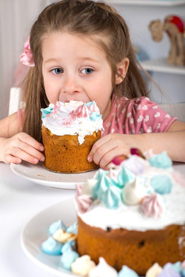 Studio strzał mały dziewczyny obsiadanie przy łasowanie Wielkanocnymi tortami i stołem obrazy royalty free