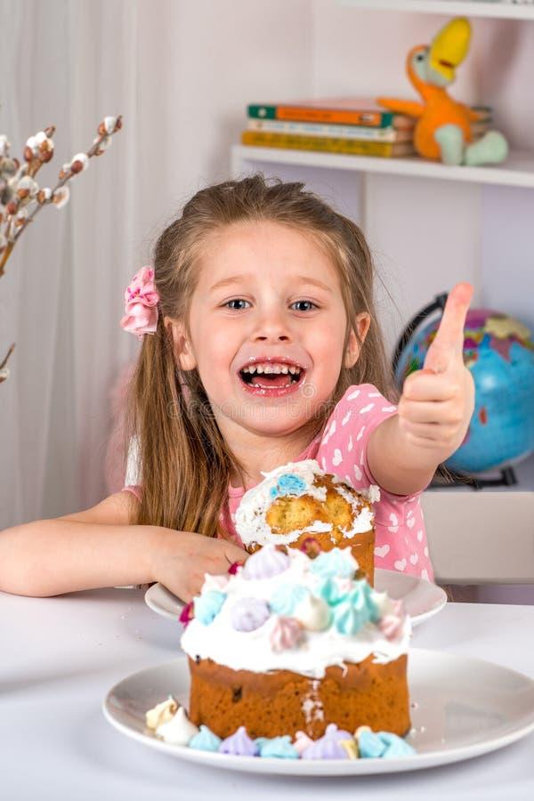 Studio strzał mały dziewczyny obsiadanie przy stołu i łasowania wielkanocą Świątecznego nastrój i gesty znak zatwierdzenie obraz stock