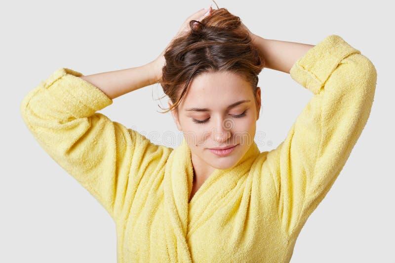 Studio strzał oferta concetrated kobieta skupiającego się puszek, zbiera włosy, jest ubranym domowego kontusz, cieszy się przy, w zdjęcia royalty free