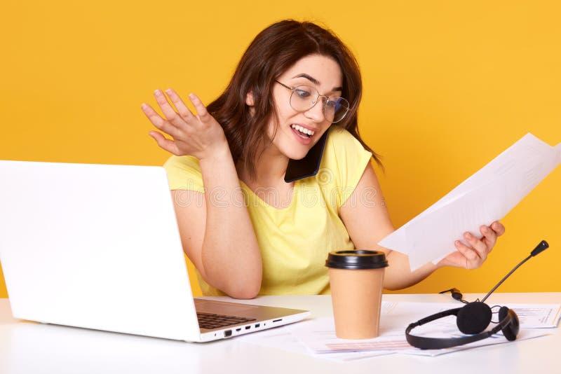 Studio strzał patrzeje dokumenty w ona uśmiechnięta kobieta ręka siedzi przy jej pracą podczas gdy opowiadający na telefonie z je obraz stock