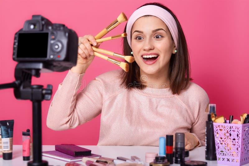 Studio strzał piękni kobiety blogger stylisty chwyty w ręka różnym kosmetyku szczotkuje, szczęśliwego wyraz twarzy, stojaki z obraz royalty free