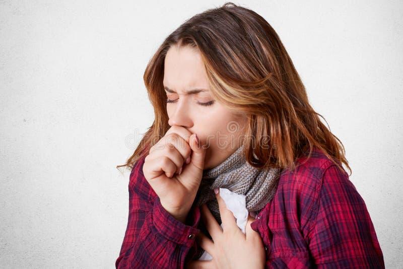 Studio strzał piękny młody kobieta model bad kasłanie, używa tkankę, jest ubranym szalika na szyi, czuje, cierpiącego i niezdrowe fotografia stock