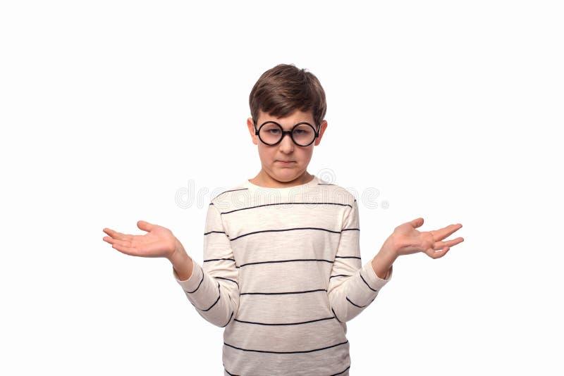 Studio strzał poważna chłopiec jest ubranym białą koszula zastanawia się coś rozprzestrzenia jego ręki strona, odosobniony na bie fotografia stock