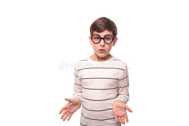 Studio strzał poważna chłopiec jest ubranym białą koszula zastanawia się coś rozprzestrzenia jego ręki strona, odosobniony na bie zdjęcie royalty free
