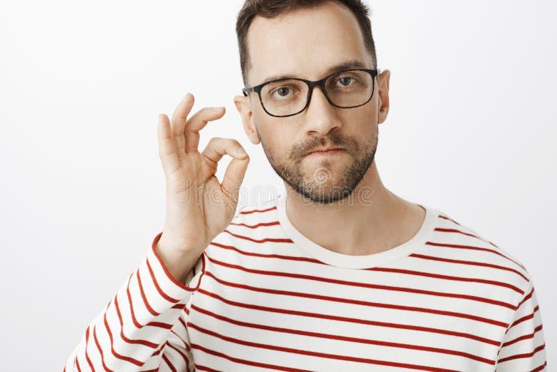 Studio strzał poważny sikający daleko gniewny mężczyzna w szkłach, zapinający usta z palcowym gestem i groźną osobą utrzymywać obrazy stock