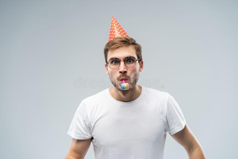 Studio strzał relaksuje i rozochocony nieogolony młody Kaukaski męski dmuchanie gwizd podczas gdy świętujący urodziny, zdjęcia royalty free