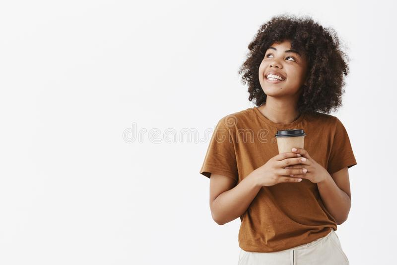 Studio strzał romantyczna marzycielska atrakcyjna dziewczyna z afro fryzurą w brown koszulki mienia papieru filiżance kawy i obraz royalty free