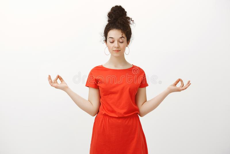 Studio strzał spokój relaksująca kobieca dziewczyna z kędzierzawym włosy czeszącym w babeczki fryzurze, rozprzestrzenia ręki w ze zdjęcie royalty free