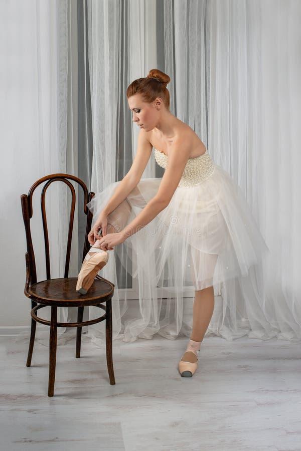 Studio strzał spokojna piękna balerina w białej powiewnej klasyk sukni stawia jej stopę na Vienna krześle i wiązać faborki na men fotografia royalty free