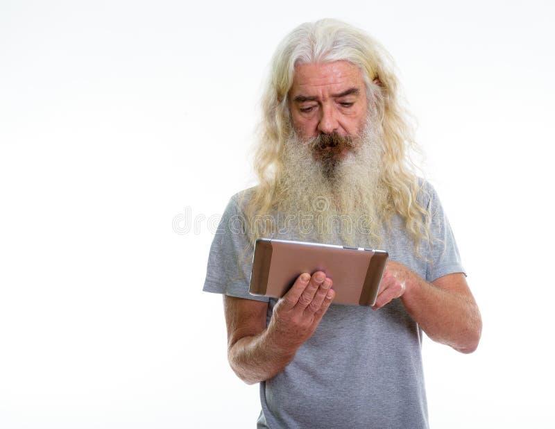 Studio strzał starszy brodaty mężczyzna używa cyfrową pastylkę i dotyka fotografia stock