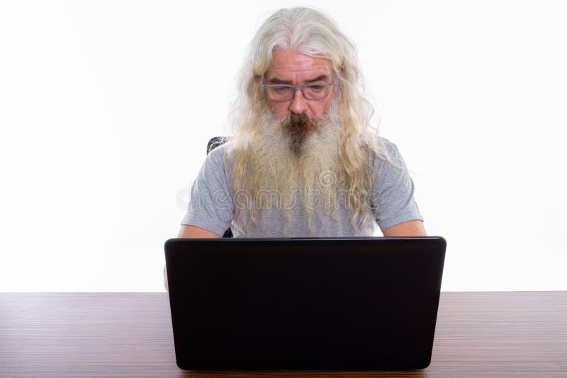Studio strzał starszy brodaty mężczyzna używa laptop na drewnianym stole fotografia stock