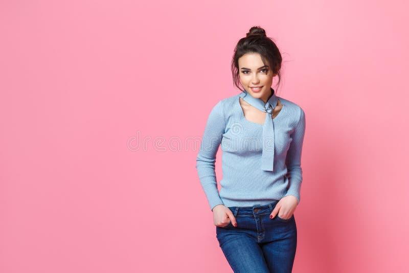 Studio strzał szczęśliwa młoda jasnogłowa kobieta ubierał niezobowiązująco cajgi i błękitną bluzkę Różowy tło kosmos kopii zdjęcie royalty free