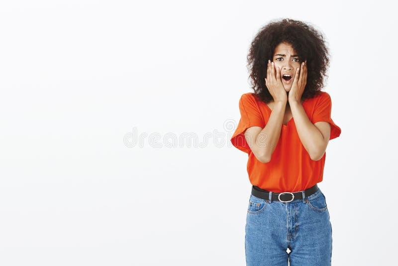 Studio strzał szokująca budzący emocje ciemnoskóra kobieta z kędzierzawego włosy mienia rękami na policzkach, zrzut szczęka od zd zdjęcie royalty free