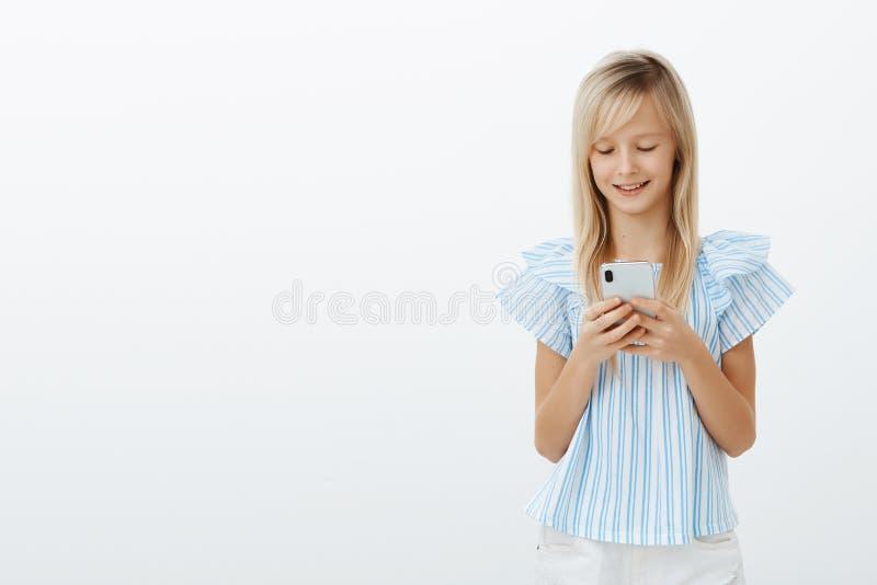 Studio strzał trzyma smartphone i ono uśmiecha się przy zadowolony atrakcyjny mały żeński dzieciak z blondynem w błękitnej bluzce obraz stock