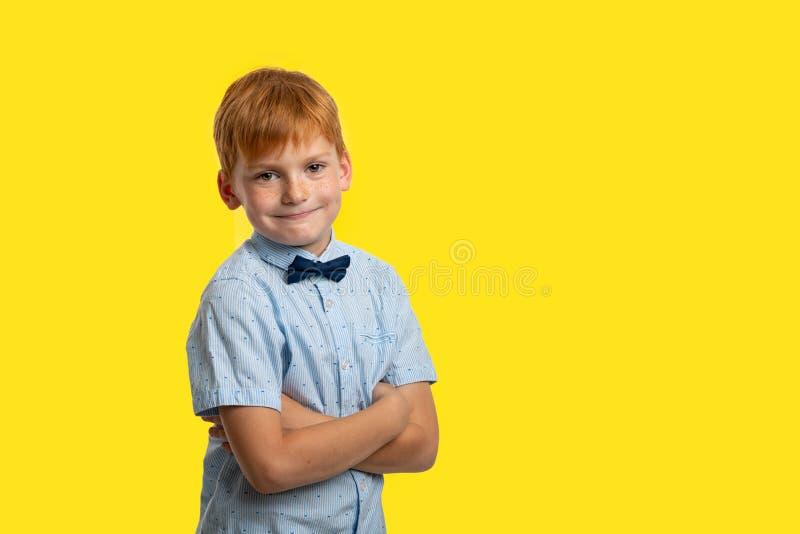 Studio strzał uśmiechnięta rudzielec chłopiec jest ubranym błękitną koszulkę z łękiem przeciw żółtemu tłu z kopii przestrzenią obrazy stock