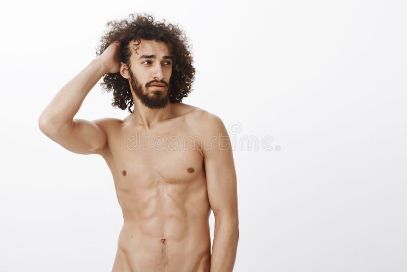 Studio strzał ufny atrakcyjny latynosa model z męskim dysponowanym ciałem, wzruszającym włosy i patrzeć na boku, czujący zdjęcie stock