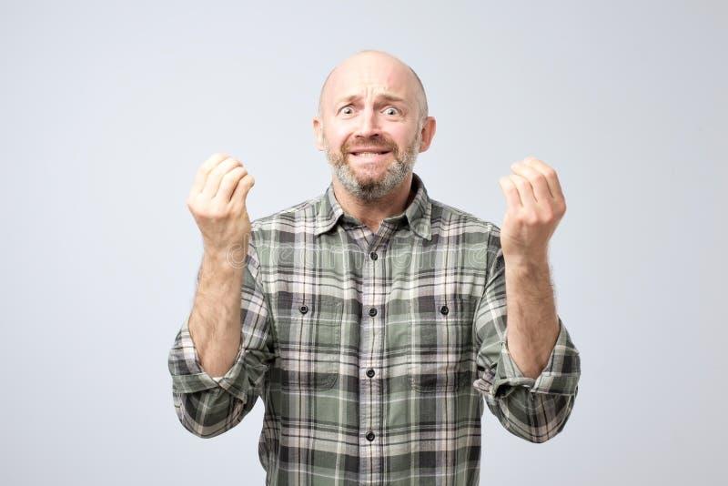 Studio strzał z podnieceniem budzący emocje dojrzałe mężczyzna ciągnięcia ręki w kierunku kamery, argumentowania i seansu pożałow zdjęcia stock
