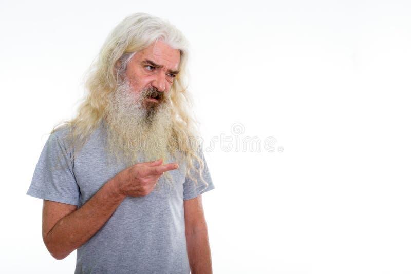 Studio strzał zdegustowany starszy brodaty mężczyzna patrzeje i wskazuje zdjęcie royalty free