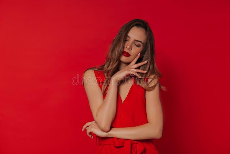 Studio strzału europejska kobieta jest ubranym czerwieni suknię pozuje nad czerwonym tłem z czerwonymi wargami zdjęcia stock
