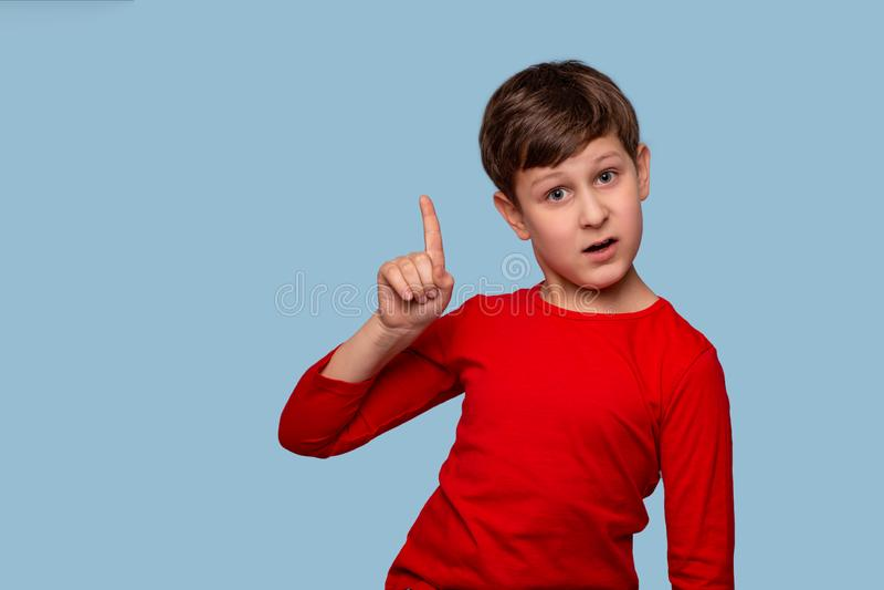 Studio strzelał chłopiec udowadnia coś odizolowywa z kopii przestrzenią podnosić jego palec wskazującego w górę, zdjęcia royalty free