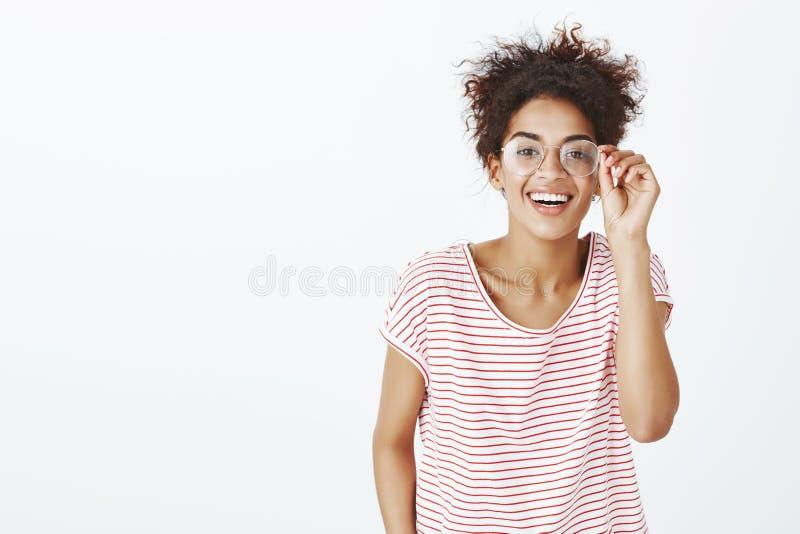 Studio strzelał śliczna beztroska atrakcyjna afroamerykańska kobieta w szkłach, trzymający obręcz eyewear i ono uśmiecha się szer zdjęcia stock