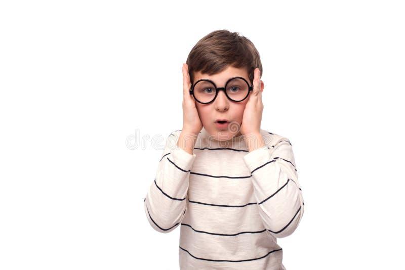 Studio strzelał śmieszna chłopiec w round szkłach, odizolowywa z kopii przestrzenią Stoi przelękłego coś i trzyma jej palmy dalej obraz stock