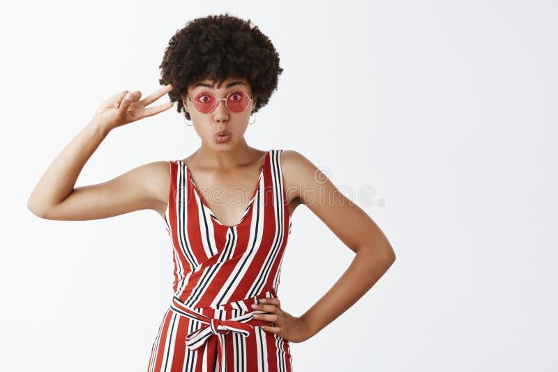 Studio strzelał atrakcyjna niemądra i figlarnie ciemnoskóra dziewczyna z kędzierzawą fryzurą, trzymający rękę na biodrze, pokazuj obrazy royalty free
