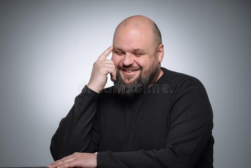 Studio strzelał gruby biznesmen ono uśmiecha się przeciw szaremu tłu Śliczny dorosły mężczyzna w czerń golfie Ekspresyjny portret fotografia stock