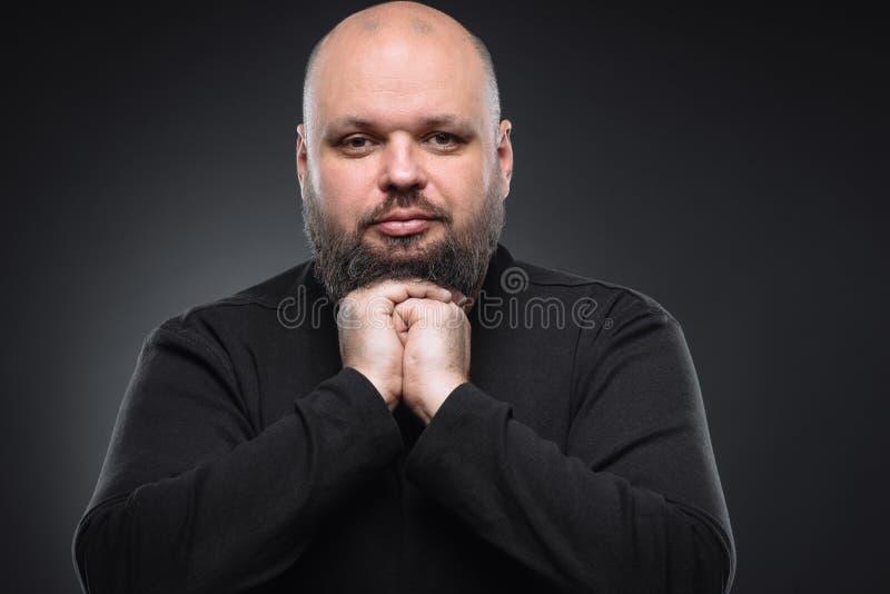 Studio strzelał gruby biznesmena główkowanie przeciw szaremu tłu Śliczny dorosły mężczyzna w czerń golfie Ekspresyjny portret fotografia royalty free