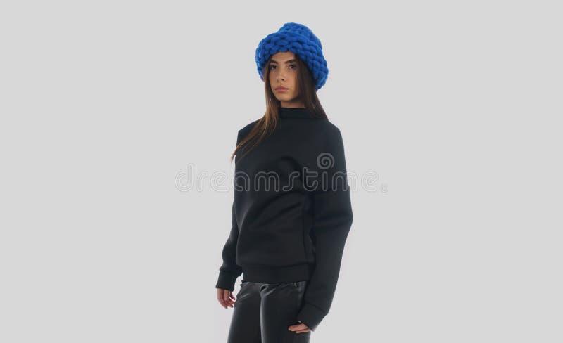 Studio strzelał młoda kobieta w chłodno zima kapeluszu i nadmiernym białym tle sweeter, odosobnionym, fotografia royalty free