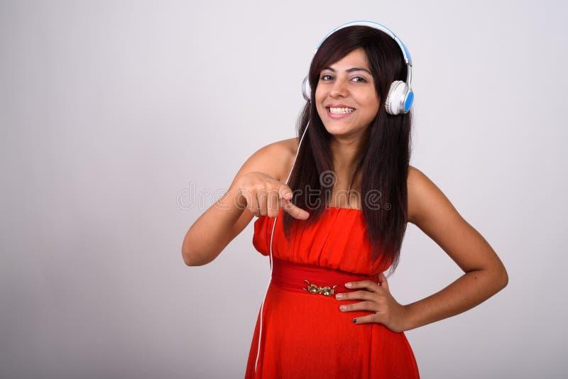 Studio strzelał młoda szczęśliwa Perska kobieta ono uśmiecha się i wskazuje przy zdjęcie stock