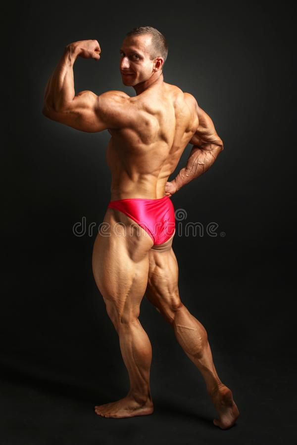 Studio strzelał młody męski bodybuilder pozuje z powrotem, przyglądający obraz stock