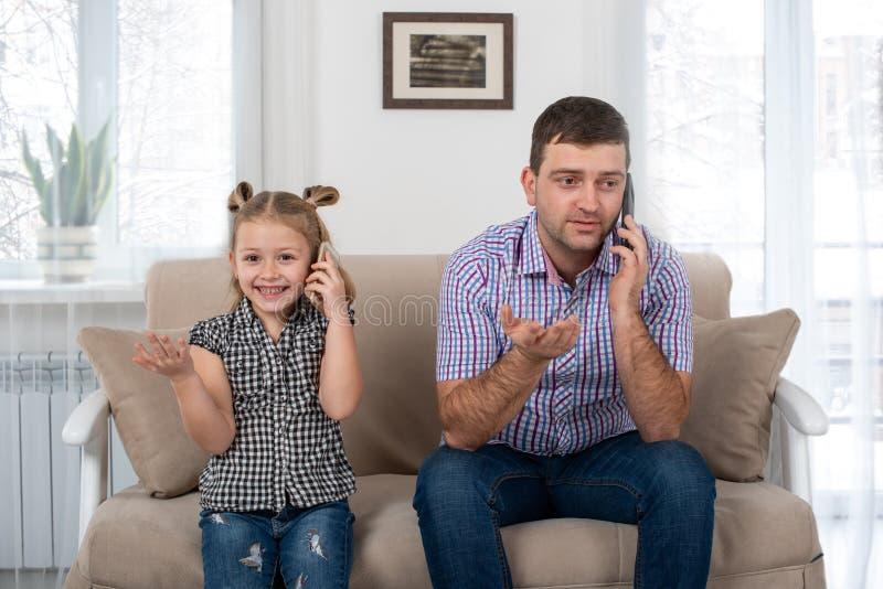 Studio strzelał małej dziewczynki obsiadanie z tatą na kanapie z laptopami w domu obrazy stock
