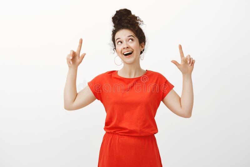 Studio strzelał marzycielska atrakcyjna kobieta z kędzierzawym włosy, patrzejący up i wskazujący z szczęśliwym radosnym wyrażenie zdjęcia royalty free