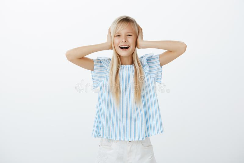 Studio strzelał niepodporządkowany dziecko stoi nad szarym tłem, nakrywkowymi ucho z palmami i zaskamlać z złym zachowaniem, obrazy stock