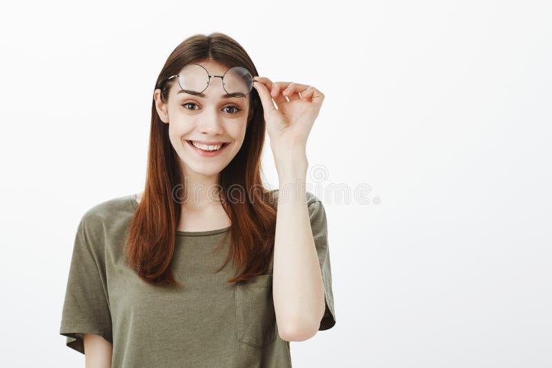 Studio strzelał radosny piękny miastowy żeński uczeń bierze daleko modnych round szkła i trzyma eyewear na czole zdjęcie stock