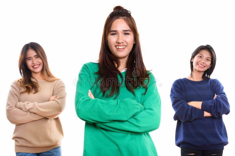 Studio strzelał trzy szczęśliwego młodego Azjatyckiego kobieta przyjaciela uśmiecha się dowcip obrazy royalty free