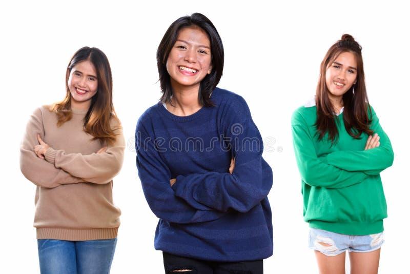 Studio strzelał trzy szczęśliwego młodego Azjatyckiego kobieta przyjaciela uśmiecha się dowcip zdjęcia royalty free