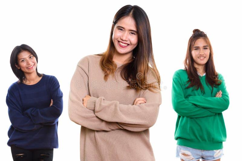 Studio strzelał trzy szczęśliwego młodego Azjatyckiego kobieta przyjaciela uśmiecha się dowcip zdjęcia stock