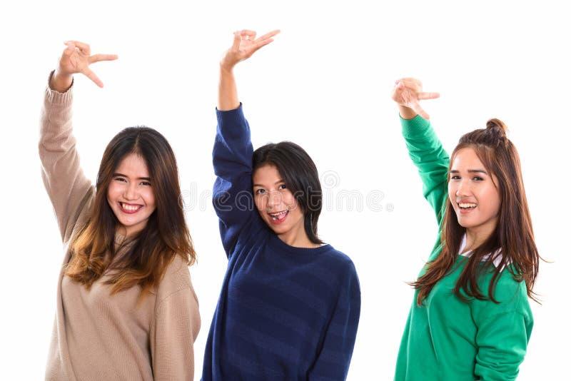 Studio strzelał trzy szczęśliwego młodego Azjatyckiego kobieta przyjaciela uśmiecha się whi obrazy stock