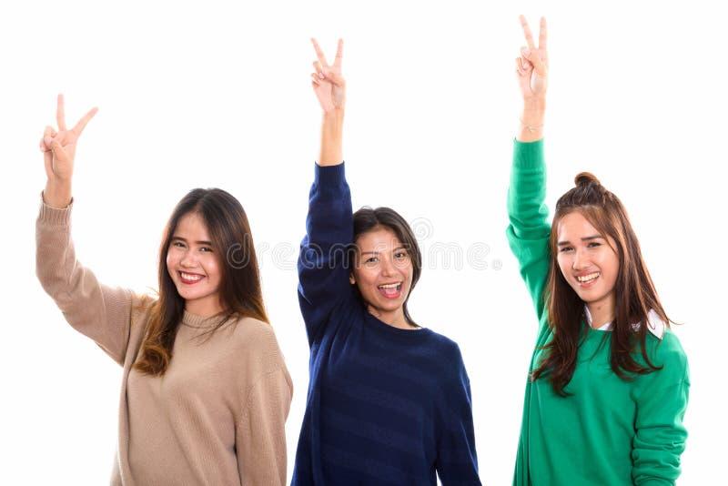 Studio strzelał trzy szczęśliwego młodego Azjatyckiego kobieta przyjaciela uśmiecha się whi zdjęcia stock