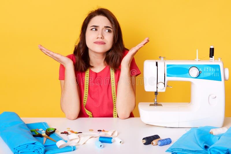 Studio strzelał tsylist dziewczyny rzemieślnika szwaczki obsiadanie przy białym biurkiem z szwalną maszyną, ścieg, igły atrakcyjn zdjęcie stock