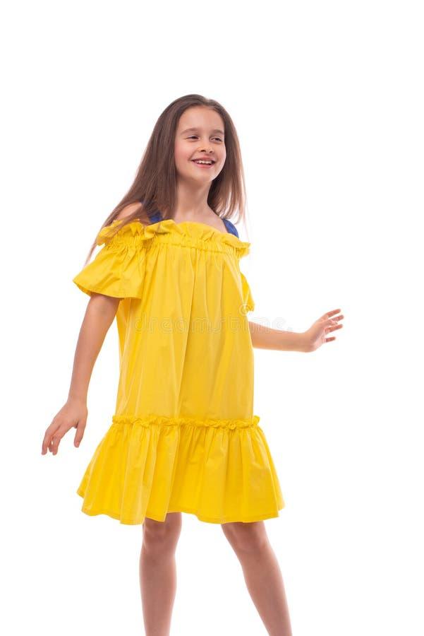 Studio strzelał uśmiechać się aktywnej dziewczyny jest ubranym żółtych sundress troszkę, odizolowywa obraz royalty free