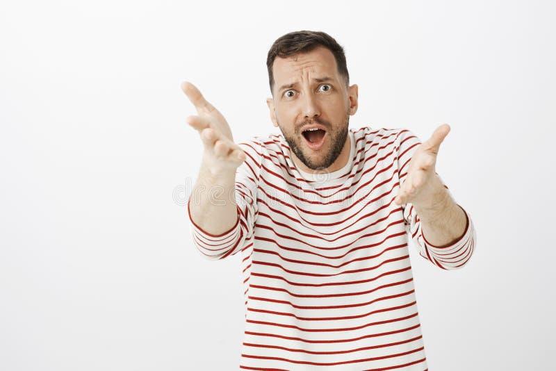 Studio strzelał z podnieceniem budzący emocje fan piłki nożnej w pasiastym pulowerze, ciągnący ręki w kierunku kamery i argumento zdjęcie stock