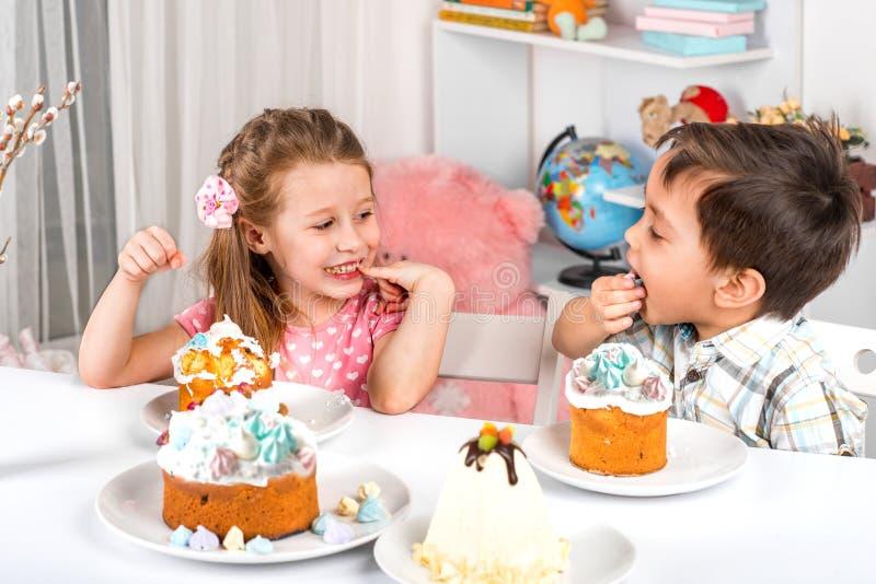 Studio strzelający mali dzieci dziewczyna i chłopiec siedzi przy stołem z Wielkanocnymi tortami, Jedzą wielkanoc z świątecznym na zdjęcia royalty free